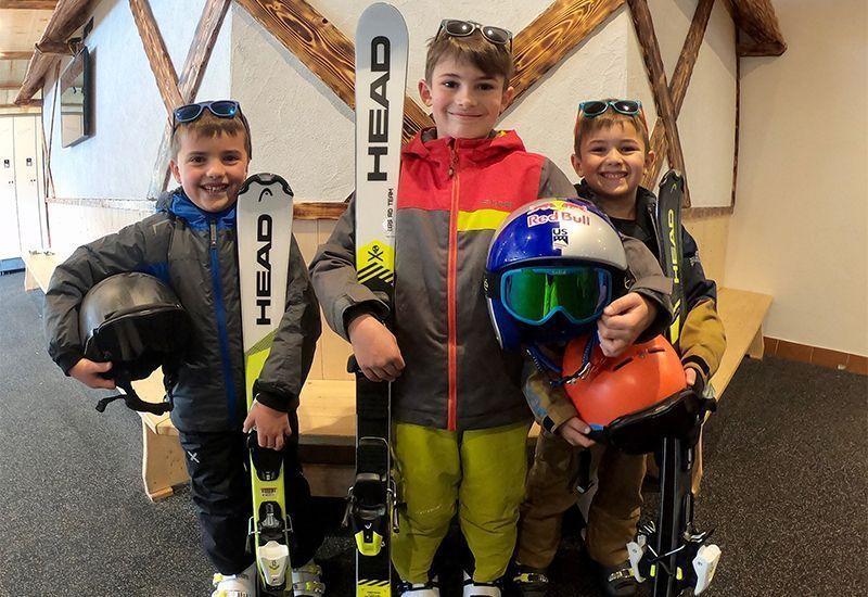 Tre bambini felici con gli sci noleggiati da Noleggio sci Andalo